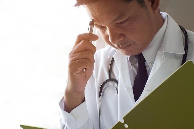 O médico pensa e enfatiza ao ler registros de pacientes.