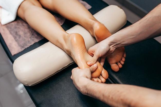 O médico podólogo faz um exame e massagem no pé do paciente na clínica.