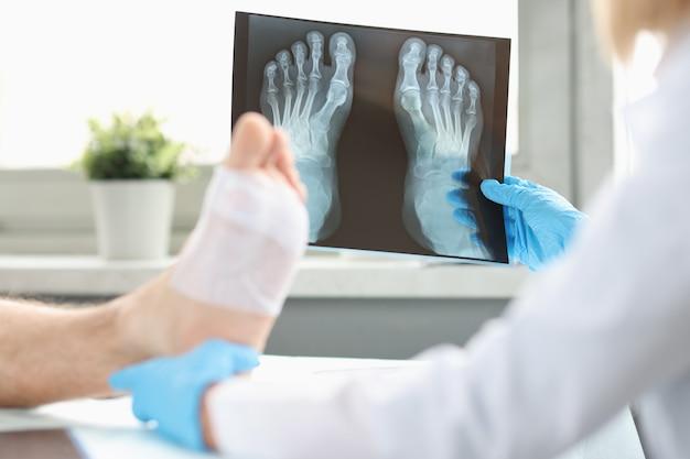 O médico realiza o exame físico do paciente com a perna enfaixada e examina a imagem do raio-x