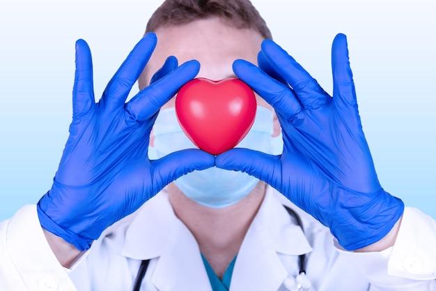 O médico segura um coração vermelho à sua frente como um símbolo de saúde.