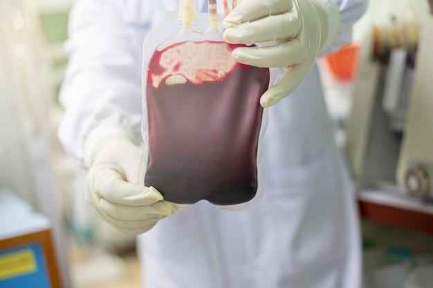 O médico segura uma bolsa de sangue para o paciente.