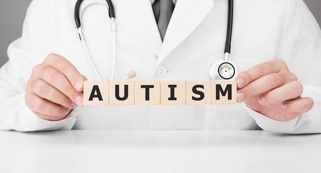 O médico tem cubos de madeira nas mãos com o texto autismo