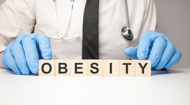 O médico tem cubos de madeira nas mãos com o texto obesidade