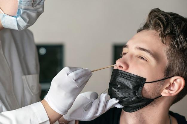 O médico tira um cotonete do nariz do jovem. teste de dna teste de pcr cuidados médicos