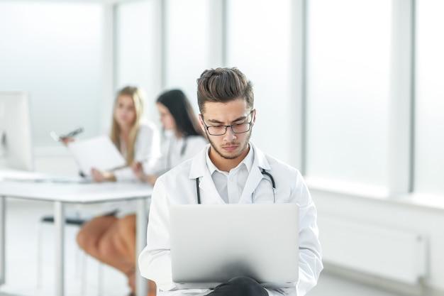 O médico trabalha em um laptop no quarto do hospital .foto com espaço de cópia