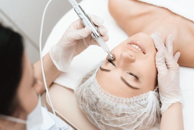 O médico trata o rosto das meninas com um photoepilator