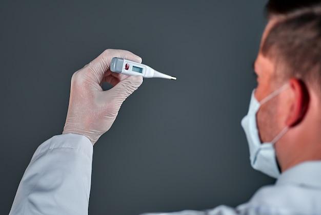 O médico usa luvas para mostrar o termômetro