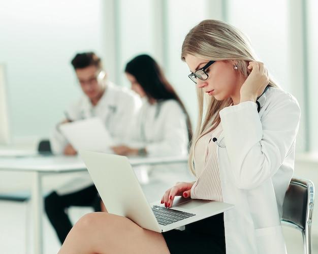 O médico usa um laptop para trabalhar com documentos