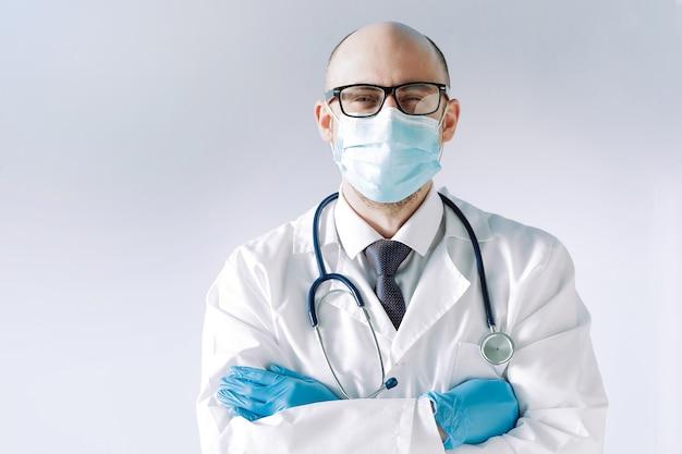 O médico usando uma máscara de proteção e luvas olha para você com confiança