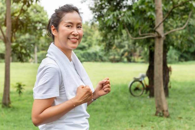 O meio asiático envelheceu a mulher que sorri e que movimenta-se no parque.