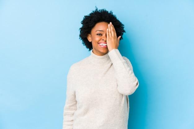 O meio envelheceu a mulher afro-americano contra uma parede azul isolada se divertindo cobrindo metade do rosto com a palma.