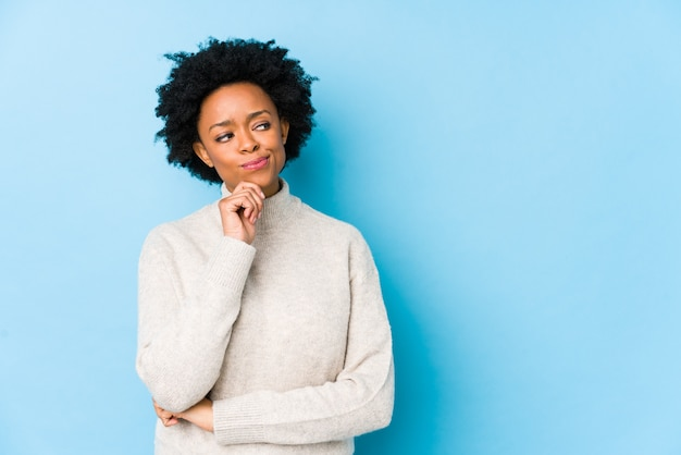 O meio envelheceu a mulher afro-americano contra uma parede azul que olha lateralmente com expressão duvidosa e cética.
