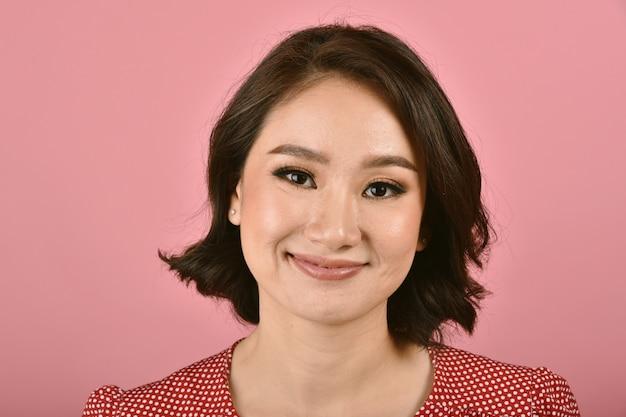 O meio envelheceu a mulher asiática de sorriso segura, os adultos de meia idade têm o problema de pele facial, sinais visíveis do envelhecimento, enrugamento, pés de galinha.
