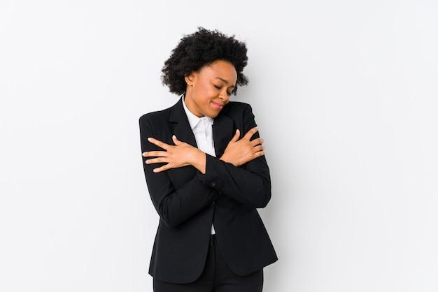 O meio envelheceu a mulher de negócio afro-americano contra uma parede branca abraços isolados, sorrindo despreocupado e feliz.