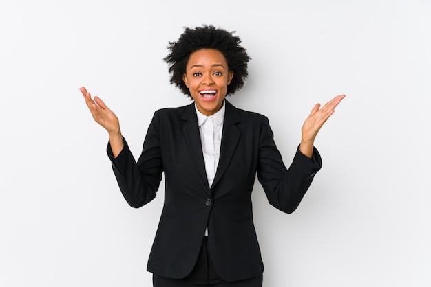 O meio envelheceu a mulher de negócio afro-americano contra uma parede branca isolada recebendo uma surpresa agradável, excitada e levantando as mãos.