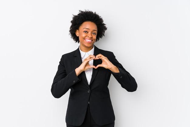 O meio envelheceu a mulher de negócio afro-americano contra uma parede branca isolada sorrindo e mostrando uma forma do coração com mãos.