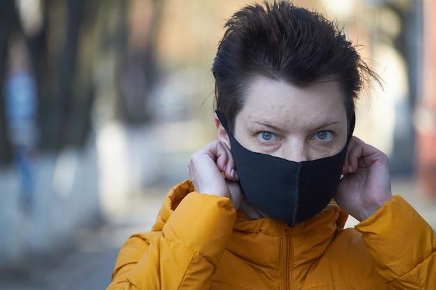 O meio envelheceu a mulher européia na máscara preta protetora, máscara vestindo da mulher durante a epidemia do coronavírus covid-19. mulher doente usando proteção durante uma pandemia.