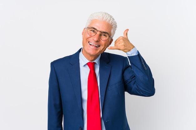 O meio envelheceu o homem de negócio caucasiano isolado mostrando um gesto de chamada de telefone móvel com dedos.