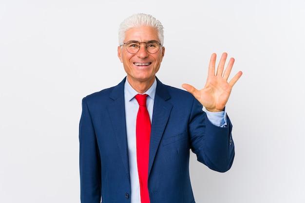 O meio envelheceu o homem de negócio caucasiano isolado sorrindo mostrando alegre número cinco com dedos.