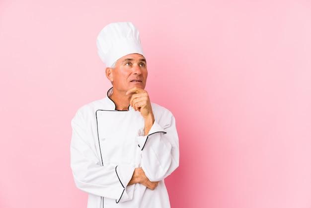 O meio envelheceu o homem do cozinheiro isolado olhando lateralmente com expressão duvidosa e cética.
