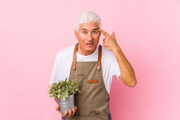 O meio envelheceu o homem do jardineiro isolado mostrando um gesto da decepção com dedo indicador.