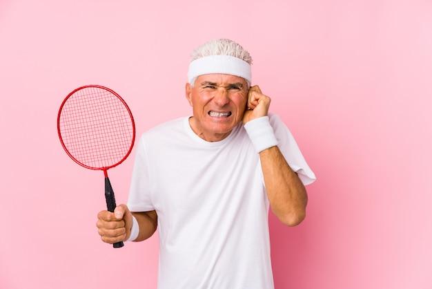 O meio envelheceu o homem que joga o badminton isolado cobrindo as orelhas com as mãos.
