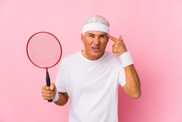 O meio envelheceu o homem que joga o badminton isolado mostrando um gesto da decepção com dedo indicador.
