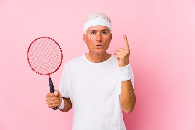 O meio envelheceu o homem que joga o badminton isolado tendo alguma grande ideia, conceito da faculdade criadora.
