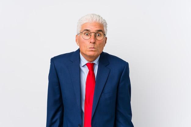 O meio homem de negócios caucasiano envelhecido isolado encolhe os ombros e abre os olhos confusos.