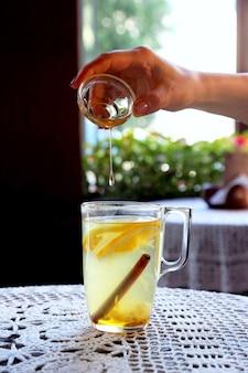O mel derrama em uma xícara de chá com limão, menta e gengibre