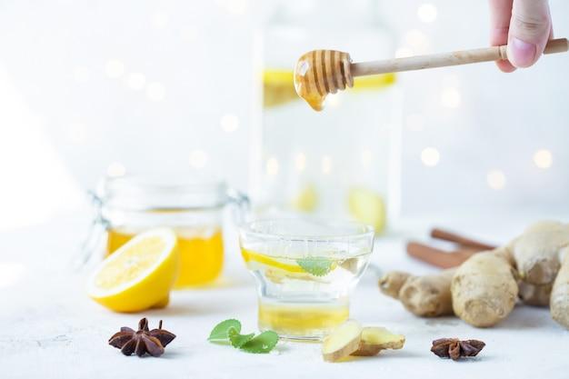O mel é derramado em uma bebida de gengibre em um copo. raiz de gengibre, mel em uma jarra, limão em uma mesa branca.