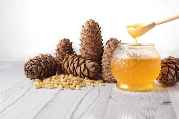 O mel é despejado de uma colher de pau em um barril de vidro, ao lado de cones de cedro e nozes em uma luz.