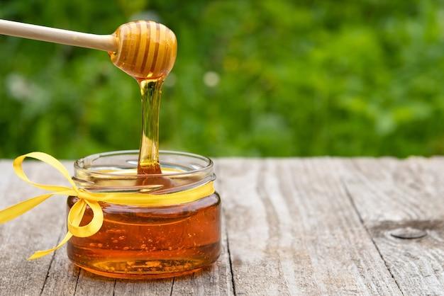 O mel pinga de uma colher de pau em um pote