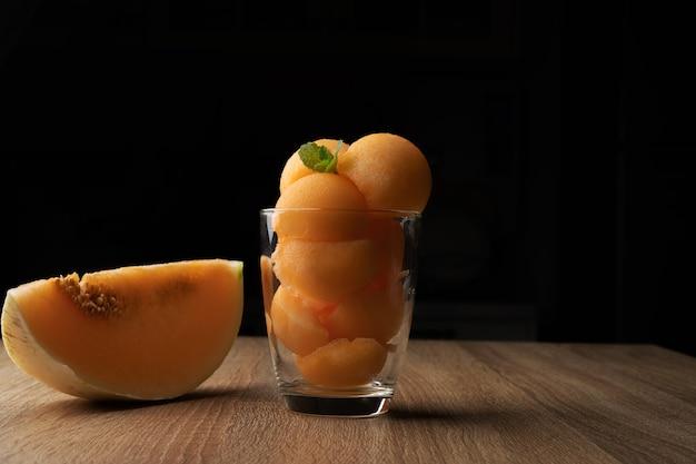 O melão de polpa amarela foi colocado em uma bola redonda como sorvete colocado em um copo transparente