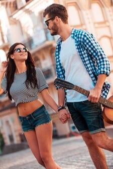 O melhor dia fora. vista de baixo ângulo de um lindo jovem casal apaixonado, de mãos dadas e olhando um para o outro, enquanto caminhava pela rua