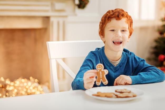 O melhor dia sempre. garoto ruivo feliz ficando animado e sorrindo amplamente enquanto comia bonecos de gengibre em uma mesa.