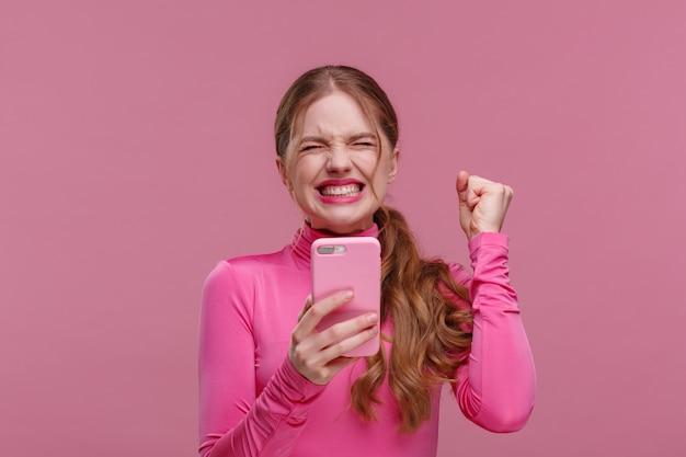 O melhor dia sempre. surpresa jovem ruiva segurando smartphone rosa, sorrindo e expressando a positividade. garota feliz tem notícias positivas chocantes. copie o espaço. jovens trabalhando com dispositivos móveis