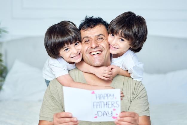 O melhor retrato de dois garotinhos latinos sorrindo para a câmera e abraçando o pai.