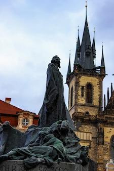 O memorial jan hus olhou para a torre da igreja tyn por trás, em um dia nublado em praga.