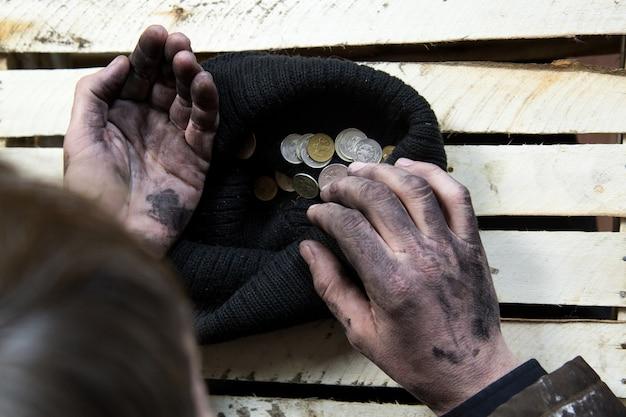 O mendigo considera moedas.