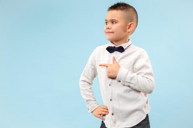 O menino adolescente feliz em pé e sorrindo contra um fundo azul.