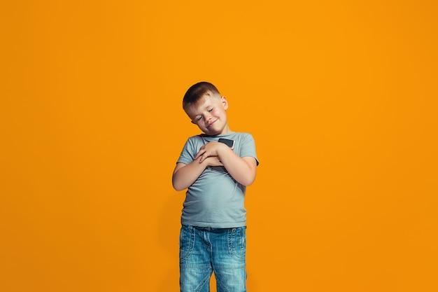 O menino adolescente feliz em pé e sorrindo contra um fundo laranja.