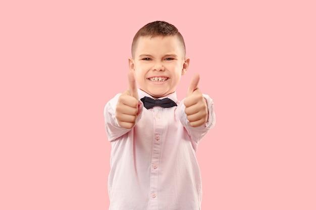 O menino adolescente feliz em pé e sorrindo contra um fundo rosa.