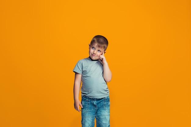 O menino adolescente feliz em pé e sorrindo