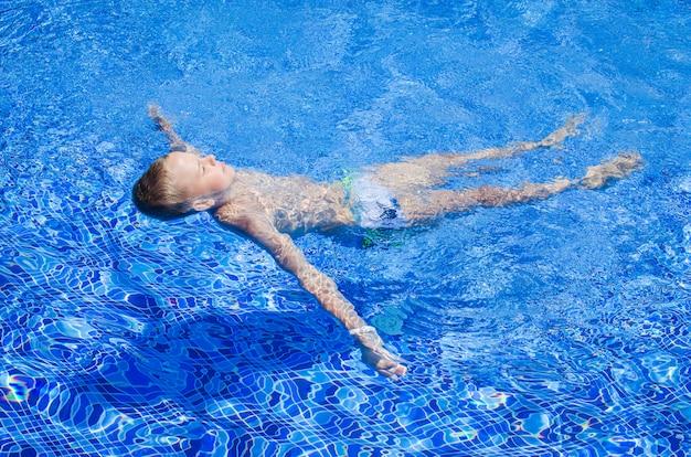 O menino adolescente feliz nada na associação no parque aquático. criança feliz nas férias de verão