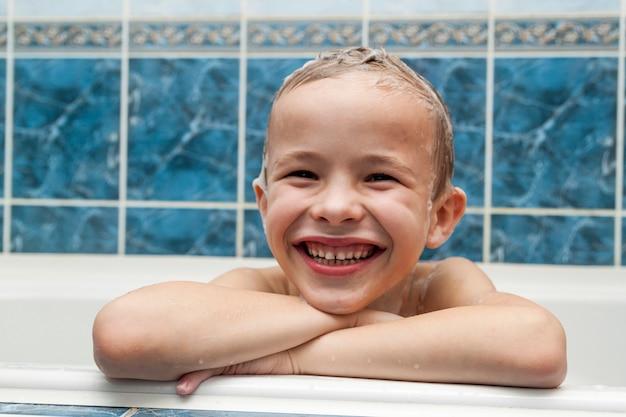 O menino adorável com sabão do champô espuma no cabelo que toma o banho. closeup retrato da criança sorridente, cuidados de saúde e conceito de higiene como logotipo. isolado no fundo branco e azul com traçado de recorte.