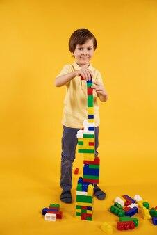 O menino alegre recolheu a torre dos blocos do brinquedo.