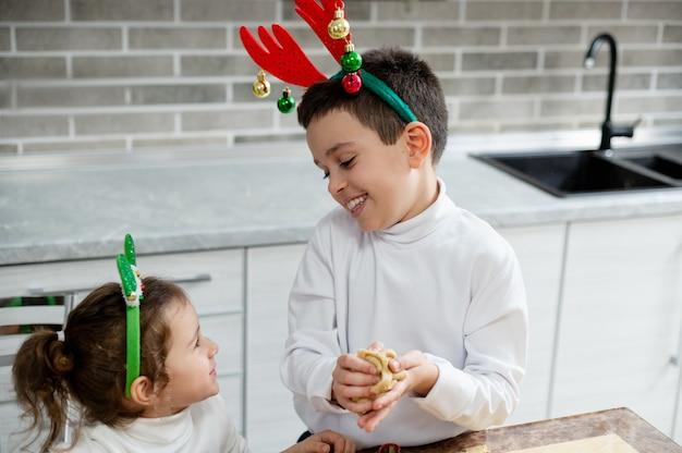 O menino amassa a massa nas mãos e sorri para a irmã mais nova