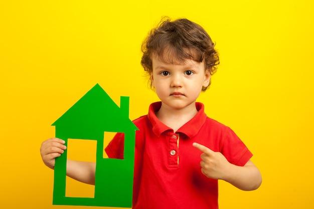 O menino aponta o dedo para o layout verde da casa. sobre um fundo amarelo.