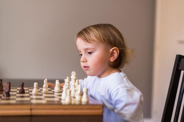 O menino aprende a jogar xadrez.